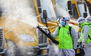 Voluntarios desinfectan autobuses escolares en Tengzhou, China.