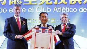 Wang Jianlin, presidente del grupo Wanda, sostiene una camiseta del Atlético de Madrid entre el director general, Miguel Ángel Gil, y el presidente, Enrique Cerezo, tras comprar un 20% del club por 45 millones de euros.