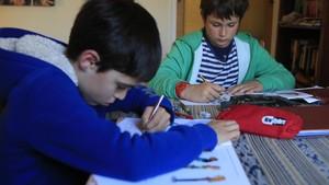 Dos estudiantes de quinto de primaria realizan sus deberes en casa de uno de ellos.