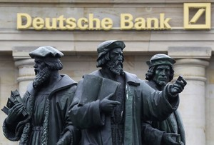 A statue is pictured next to the logo of Germanys Deutsche Bank in Frankfurt