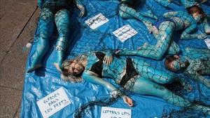 Activistas veganos con el cuerpo pintado de azul y dentro de redes de pesca, en Saint-Michel (París), el 20 de mayo.