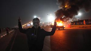 Un aficionado con máscara, junto a un coche en llamas en el exterior del estadio de la Defensa Aérea, en el este de El Cairo.