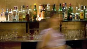 Una mujer, delante de la barra de un bar llena de bebidas.