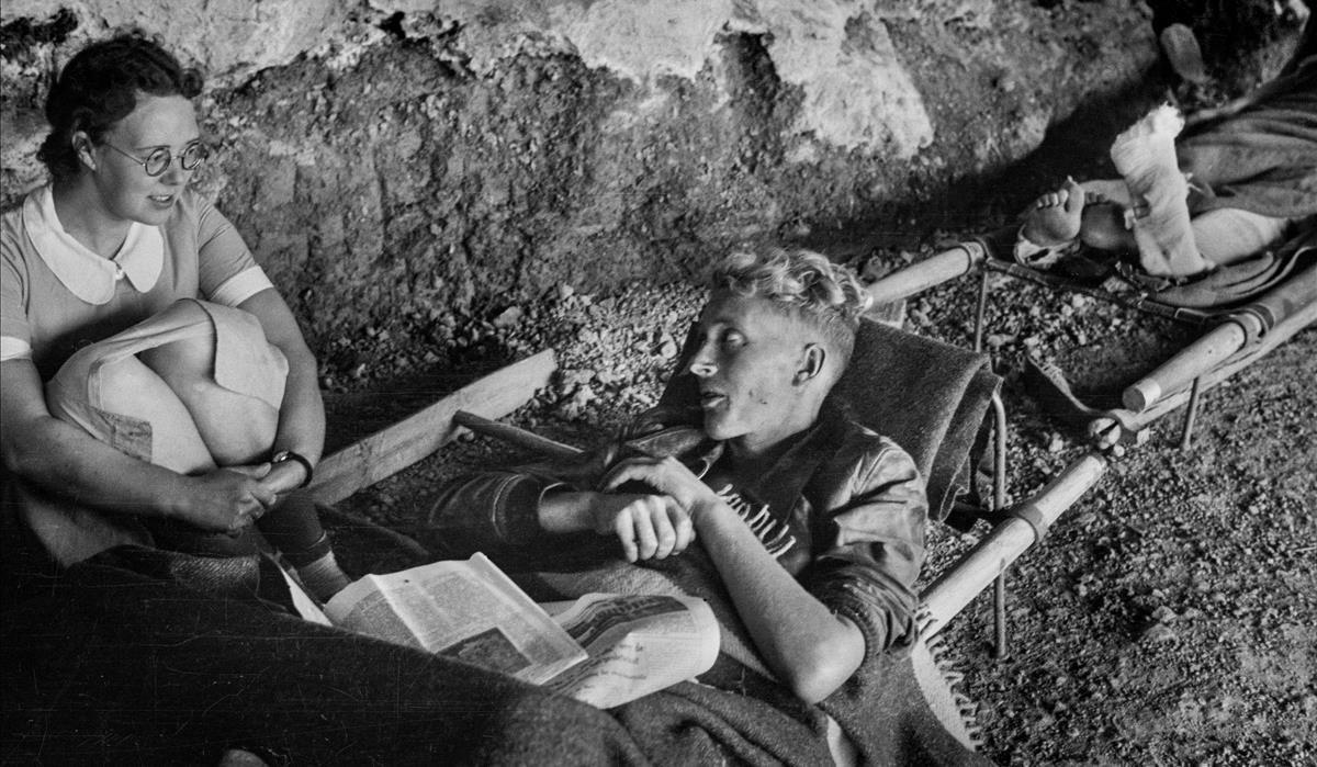 La enfermera Margaret Culpeper habla con un herido en la Cova de Santa Llúcia (La Bisbal de Falset), convertida en hospital de campaña durante la batalla del Ebro.