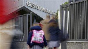 Alumnos del colegio santa María la Blanca, de Montecarmelo (Madrid), entran esta mañana en el centro.