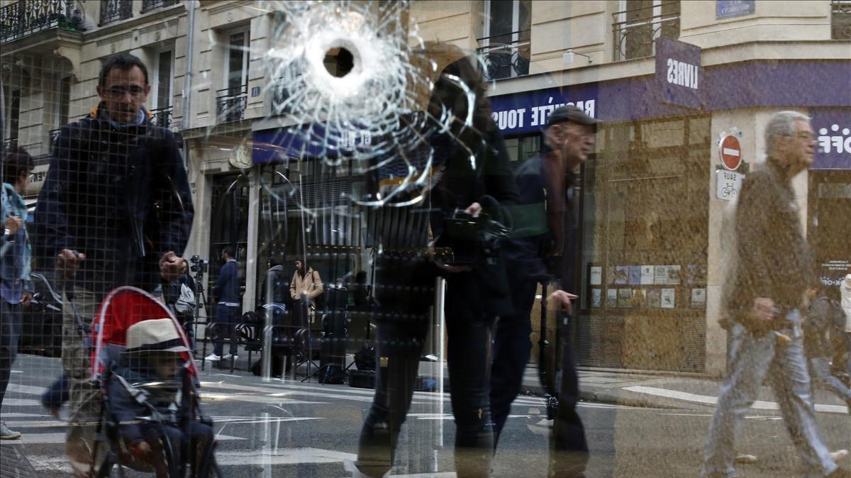 Un grupo de parisimos mira un cristal roto por un impacto de bala de la policíaen el lugar del atentado.
