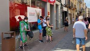 Clientes hacen cola ante la puerta de un banco, este agosto.