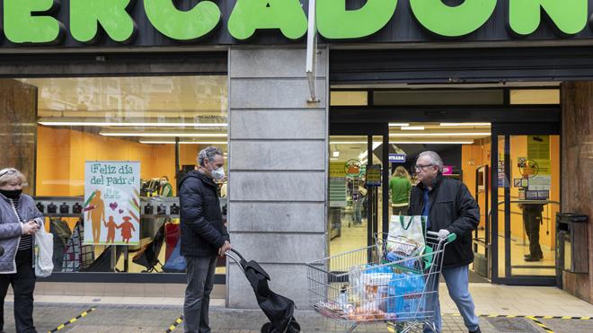 Ciudadanos hacen cola guardando la distancia de seguridad para entrar en un Mercadona de Valencia.
