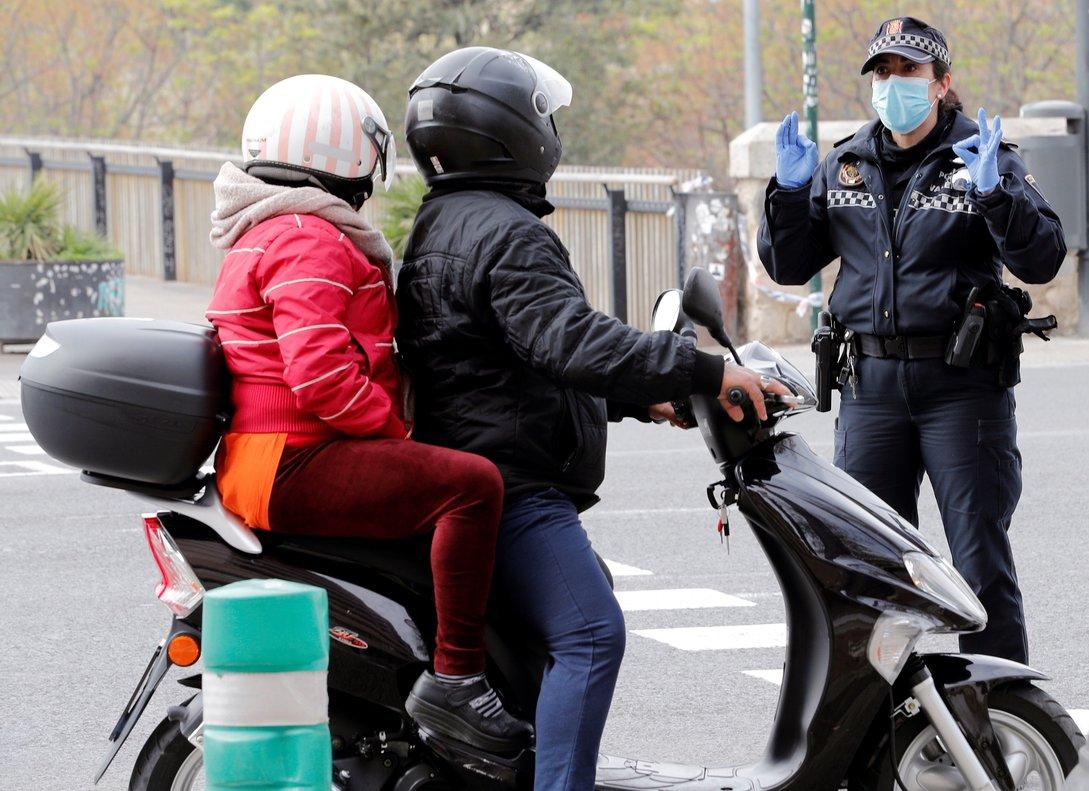 Un policía para a una pareja en moto en Valencia.