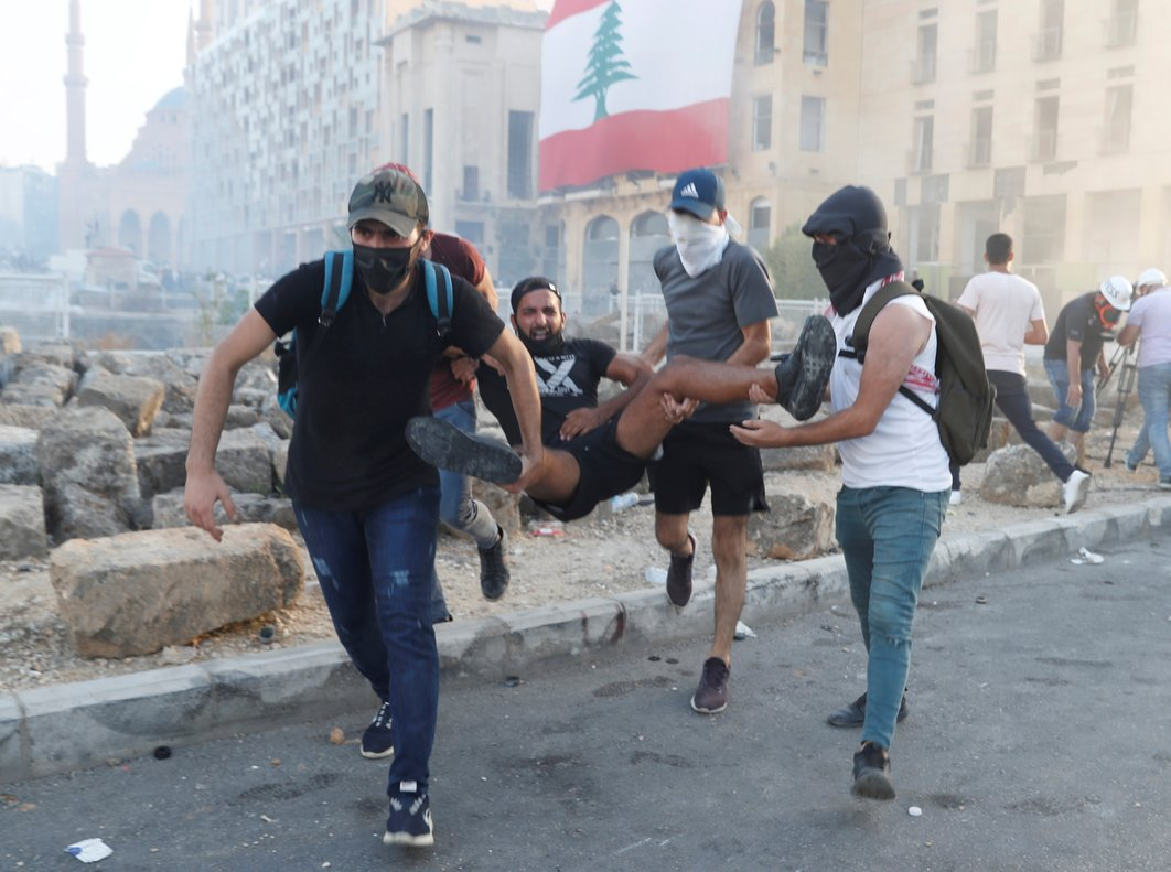 Demonstrators carry an injured man during a protest in Beirut, Lebanon, August 8, 2020. REUTERS/Goran Tomasevic