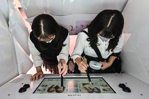 Dos chicas se toman fotos en una máquina de 'purikura', en Tokio, a finales de julio.