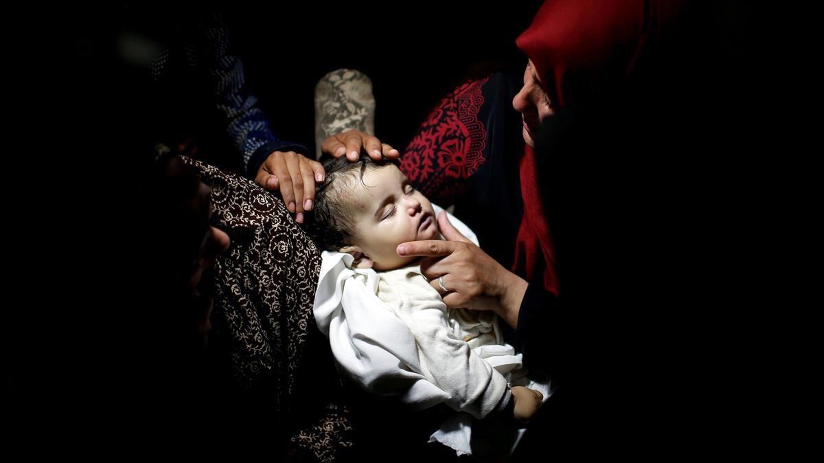 Familiares anteel cuerpo de la niña palestina Laila al-Ghandour, de ocho meses, que murió después de inhalar gas lacrimógeno durante una protesta contra el traslado de la embajada estadounidense a Jerusalén en la frontera entre Israel y Gaza.
