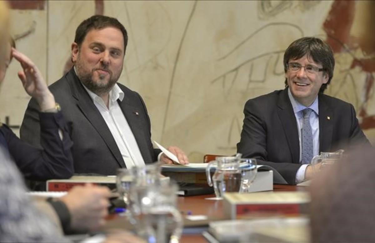 El 'president' Carles Puigdemont y el vicepresidente Oriol Junqueras, durante la reunión del Govern.