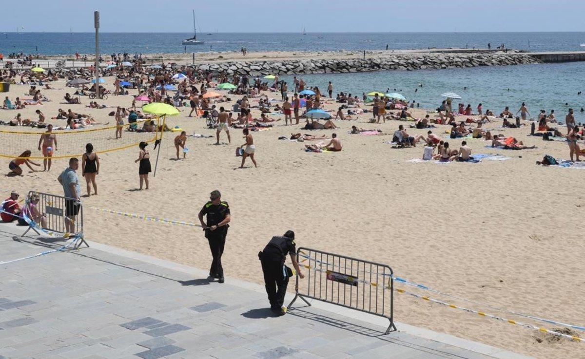La Guàrdia Urbana delimita con cintas el acceso a la playa del Bogatell, en Barcelona.