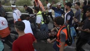 Médicos y manifestantes evacuan a un herido durante las protestas en Erez este martes.