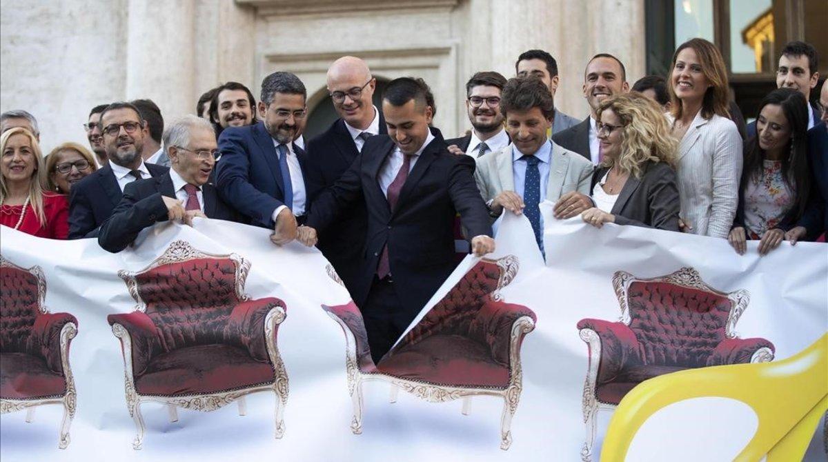 Di Maio (centro) y otros políticos rasgan una pancarta ilustrativa sobre la reforma para reducir el número de parlamentarios en Italia.