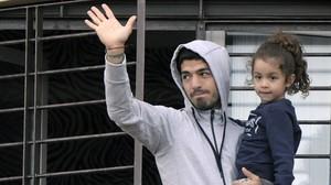 Luis Suárez saluda a los aficionados uruguayos desde el balcón de su casa con su hija.