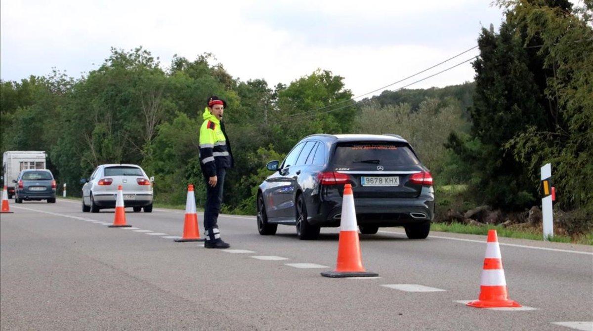 Un mosso regula el tráfico en la N-II a su paso por Bàscara, tras el accidente de una furgoneta.
