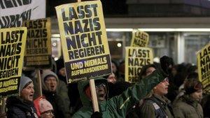 Un grupo de manifestantes con eslóganes anti-nazis protestan contra el baile en el palacio de Viena.