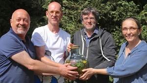 Puigdemont muestra una botella con la ratafía de Waterloo.