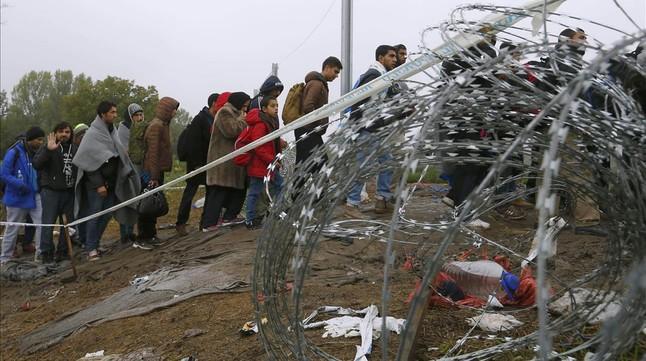 Refugiados cruzando la frontera entre Hungría y Croacia después de llegar en tren a la ciudad croata de Botovo.
