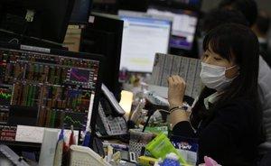 Una agente de bolsa trabaja con máscara protectora en Seúl.