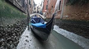 Una gondola permanece amarrada en un canal practicamente sin agua en Venecia.