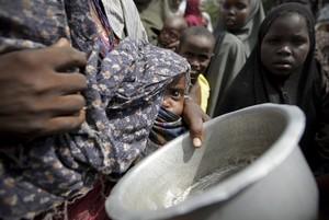 Una mujer con su bebé mientras hace cola para conseguir alimentos en un campamento para los desplazados de Mogadiscio (Somalia)