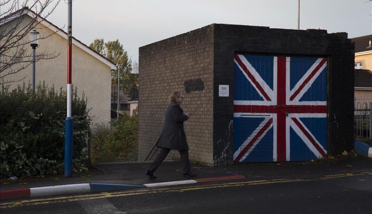 Una mujer pasa junto a un muro que luce la bandera de la Union Jack, en el barrio de Fountain West, en la localidad norirlandesa de Derry.
