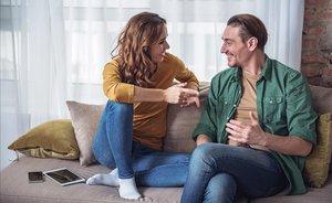 Una pareja hablando en el sofá.