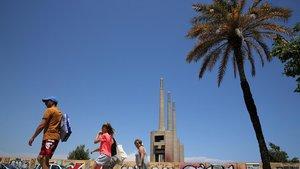 Unas personas pasan por delante de Les Tres Xemeneies de Sant Adrià de Besós, en julio del 2018.