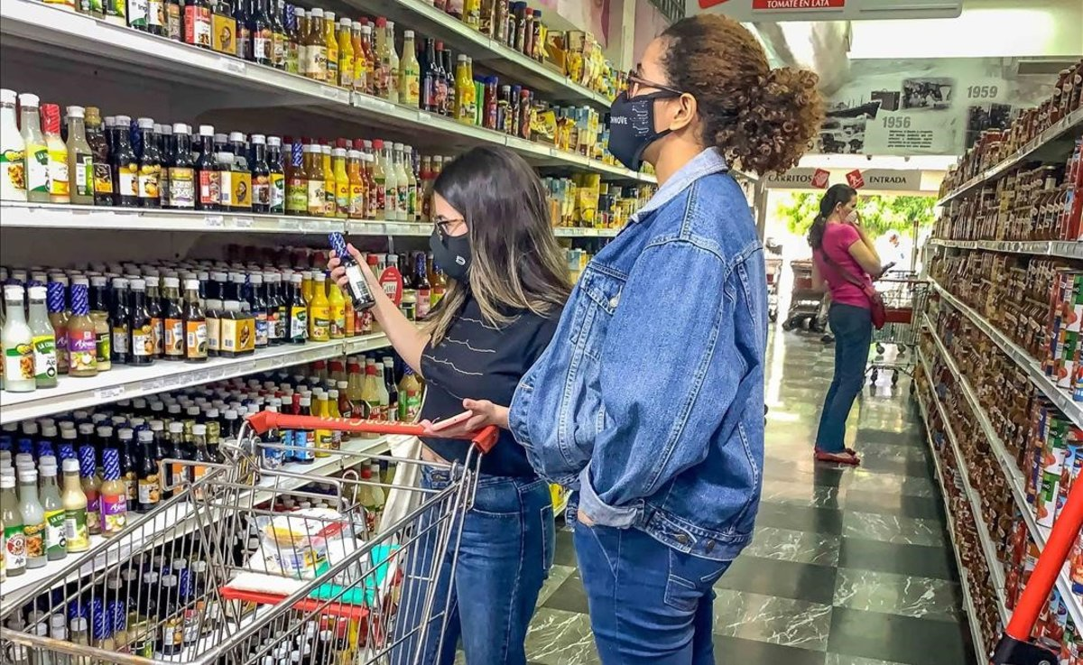Varias mujeres escogen productos en un pasillo de un supermercado el 15 de octubre de 2020en Caracas (Venezuela).