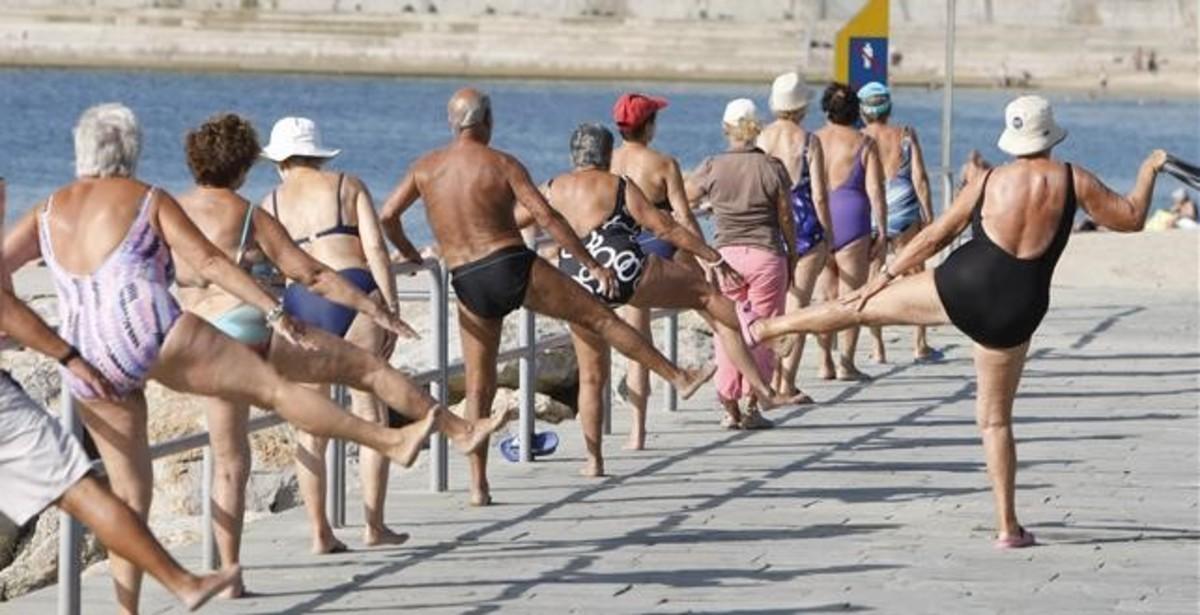 Un grupo de gente mayor hace ejercicio en el espigón de las playas del Botagell y Nova Icària.