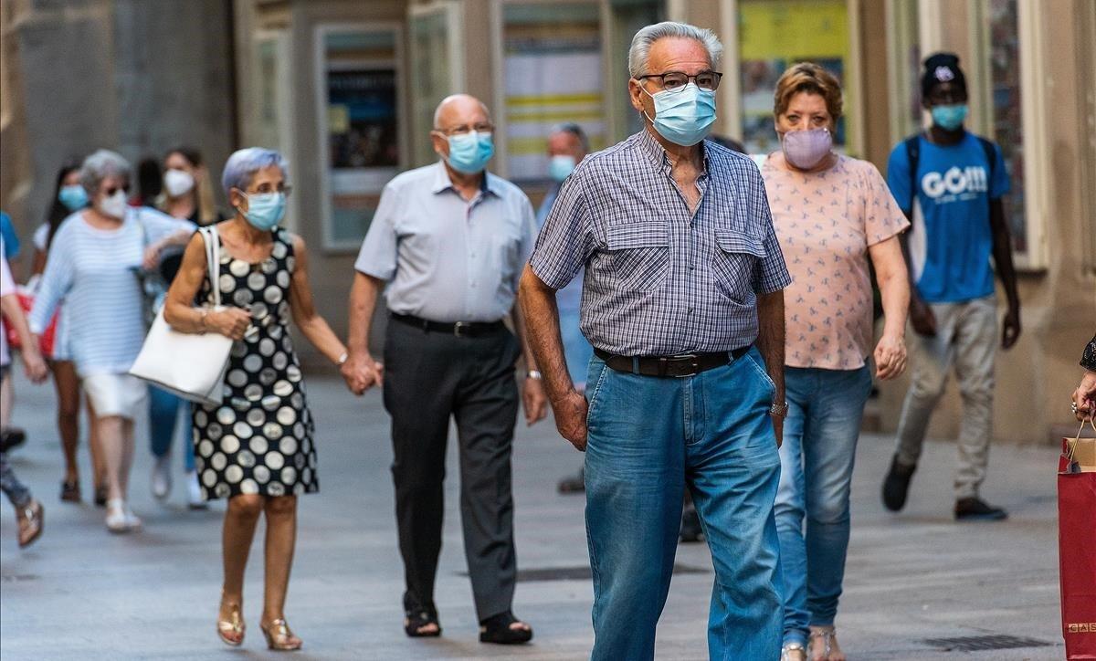 Personas mayores con mascarilla pasean por el Eix Comercial de Lleida, este martes.