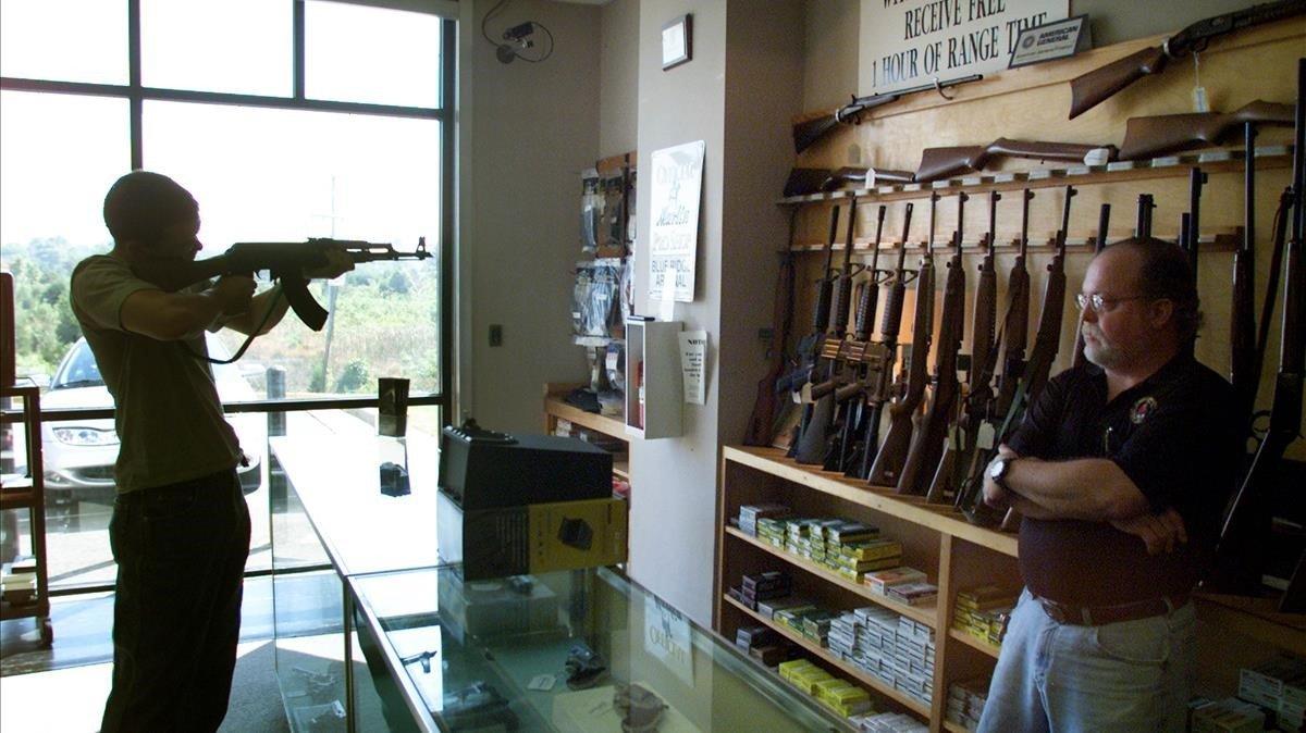 Un hombre prueba un rifle en una tienda de armas.
