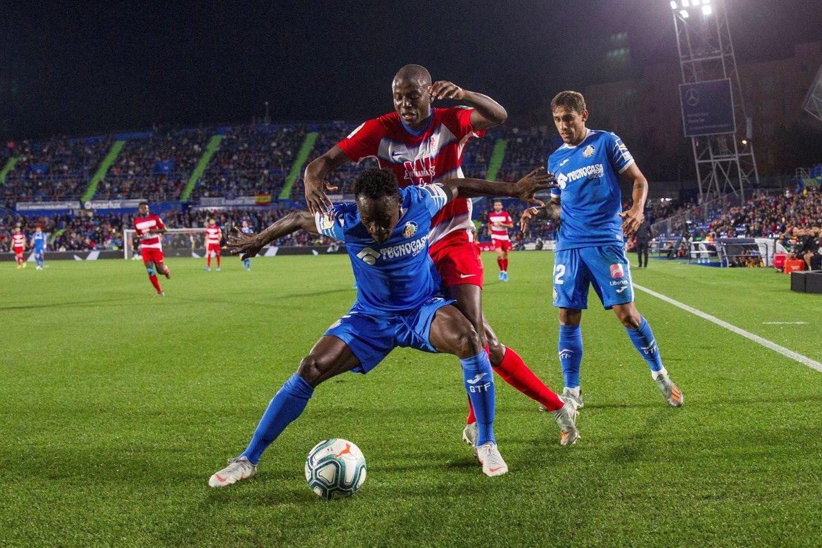 El jugador del Getafe Djene protege un balón ante el delatero del Granada Adrián Ramos.