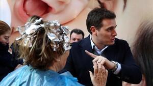 Albert Rivera saluda a una señora que ha salido de la peluquería con esta mientras se hacía las mechas.