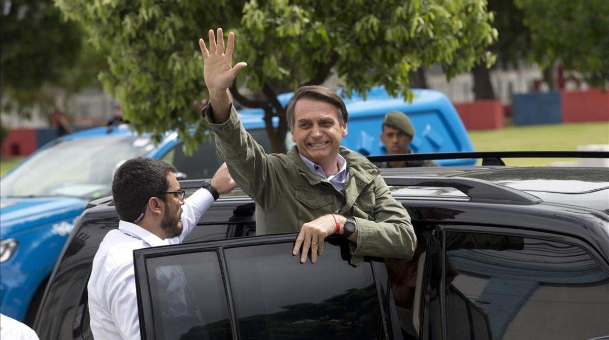 Bolsonaro saluda a sus seguidores tras depositar su voto.