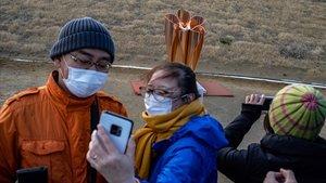 Ciudadanos japoneses se hacen fotos con la llama olímpica, recién llegada de Grecia, en Ishinomaki.