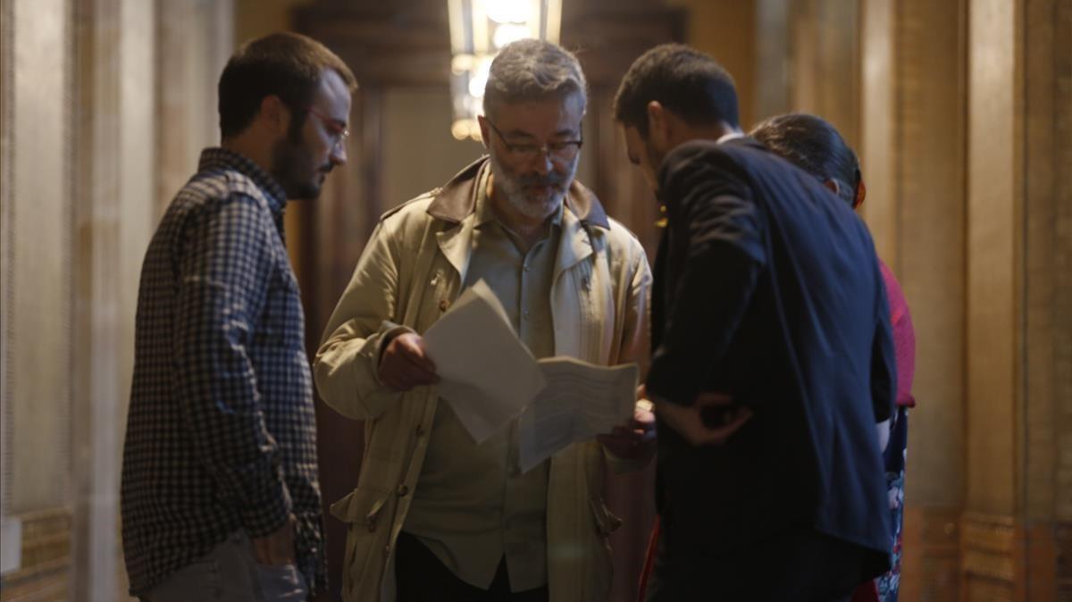 El diputado de JxSí, Roger Torrent, muestra unos documentos a los parlamentarios de la CUP Albert Botran y Carles Riera.