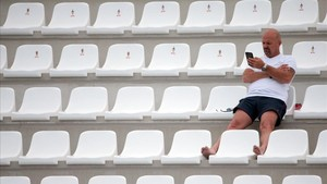 Un espectador aguarda el inicio de los partidos de waterpolo en Tarragona.