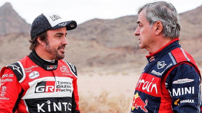 Fernando Alonso y Carlos Sainz conversan tras finalizar la etapa de hoy en el Dakar.