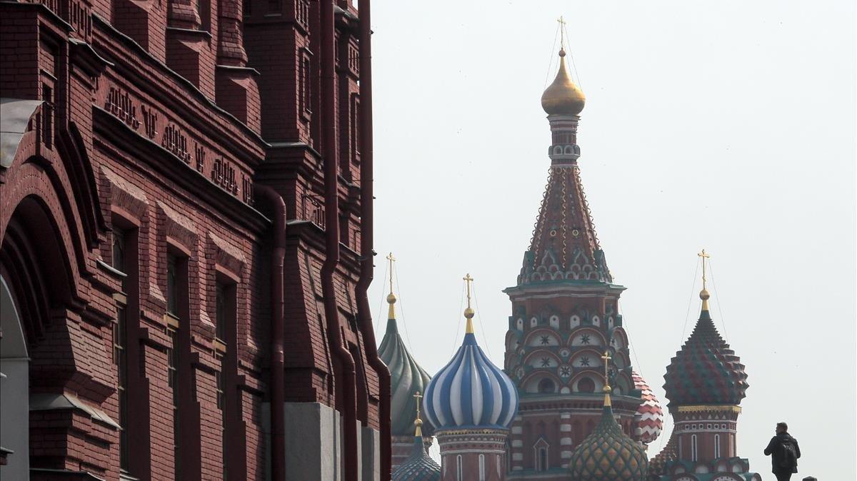 Una persona camina en frente a la catedral de Moscú en la Plaza Roja.