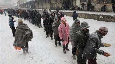 Immigrants reben menjar a l'exterior d'un magatzem duaner abandonat a Belgrad (Sèrbia).