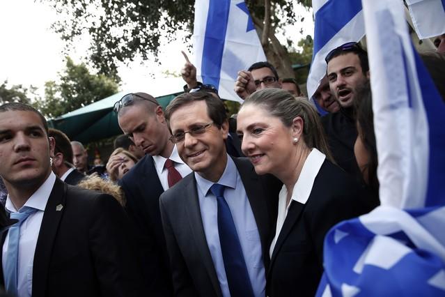 Isaac Herzog abandona, acompañado de su esposa y rodeado de seguidores, el colegio electoral donde ha votado, en Tel-Aviv.