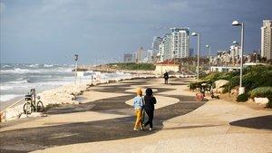 Tres personascaminan por el paseo marítimo de Tel Aviv vacío el pasado martes.