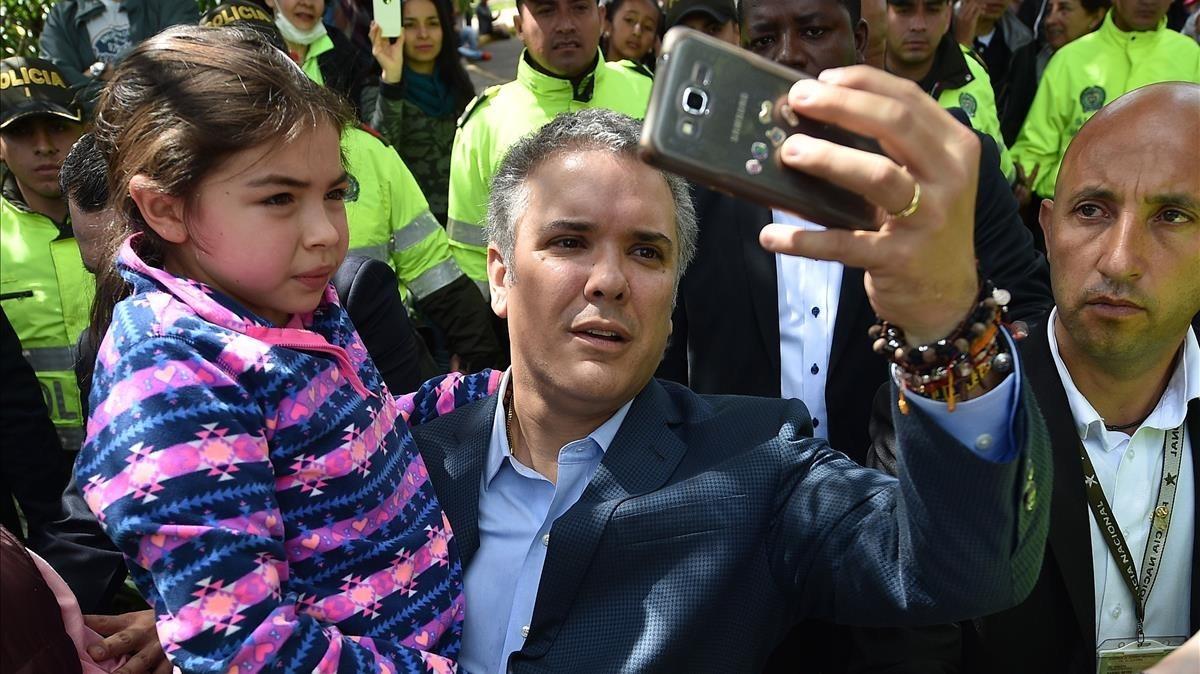 Iván Duque se hace un selfiecon una niña tras votar en Bogotá.