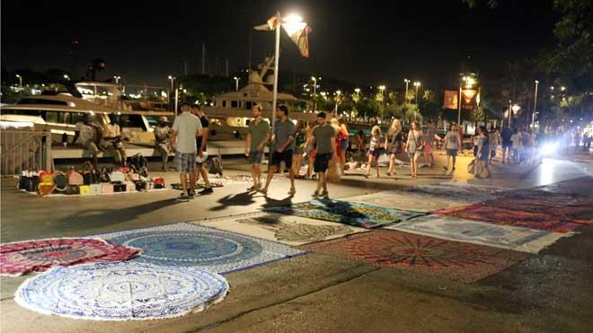 Los manteros vuelven al Port Vell por la noche, tras la retirada de la policía.