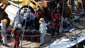 Miembros de los servicios de rescate recuperan el cuerpo de una de las victimas mortales del barco naufragado en el río Danubio.