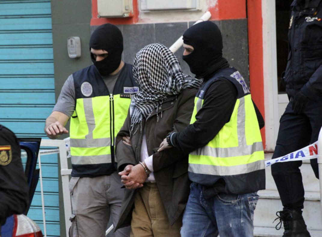 La policía traslada a un detenido en una operación yihadista.